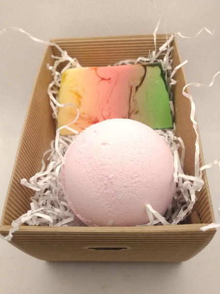 view showing contents of gift set without lid shows a handmade soap slice yellow pink and green in colour and a large pink bath bomb on a bed of white shredded paper in a brown gift box