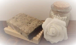Black and white coloured soap slice on soap dish displayed next to rose and candle