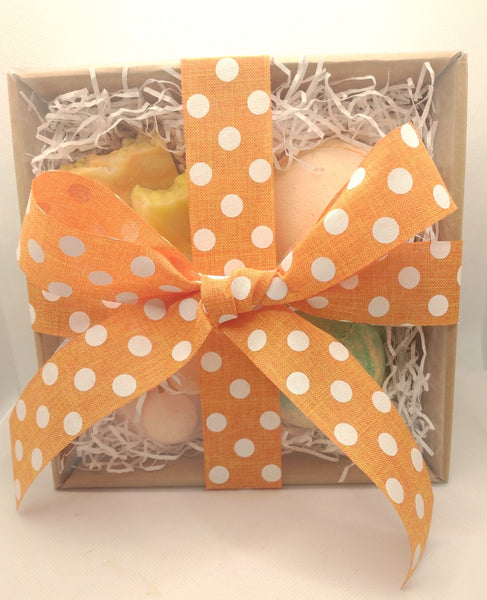 View showing the gift box from above  a brown fraft gift box with products shown through clear lid and beautiful large orange and white polka dot patter ribbon in a cross and tied off in a bow