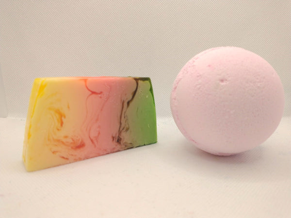 Set on a white background showing handmade soap slice yellow pink and green in colour and a large pink bath bomb