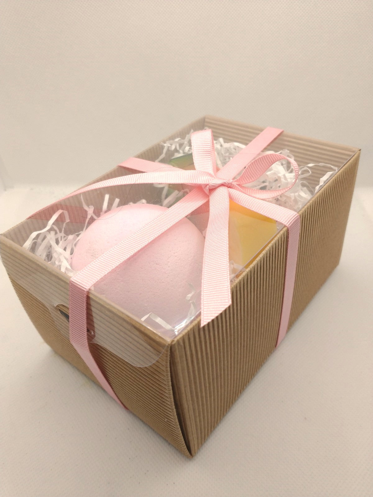 Displaying packaged bath bomb and handmade soap gift set in a brown corrugated kraft gift box with a a clear lid and a hand tied pink ribbon