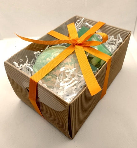 View showing packaged gift box of a brown kraft gift box with clear lid and hand tied orange ribbon tied off in a bow showing contents through clear lid
