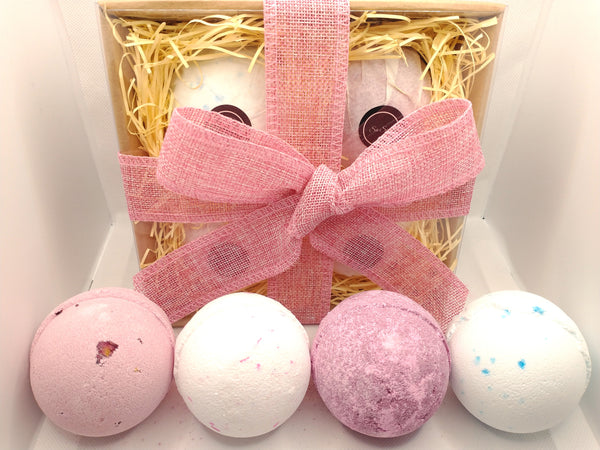 A beautifully hand tied gift set showing a kraft brown gift box containing wrapped bath bombs with logo s6 soap and a hand tied pink ribbon tied off in a bow,  contents of set shown in front of the gift set shows 4 large bath bombs 1 pink with petals 1 white with pink flecks 1 a deep cherry red and one white with blue flecks