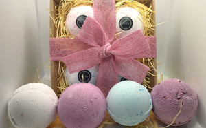 Bath Bomb Gift Set showing wrapped bath bombs on straw in a kraft gift box with hand tied ribbon and contents shown displayed in front of unpackeged items