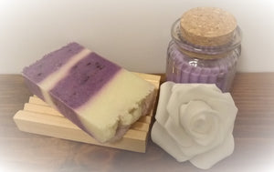 Lavender Soap slice on soap dish displayed next to rose and candle