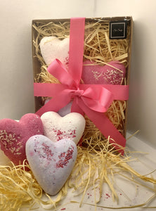 Bath Bomb Gift Set containing 3 heart shaped bath bombs displayed on straw in a kraft gift box with handtied pink ribbon and 3 heart bath bombs shown in front
