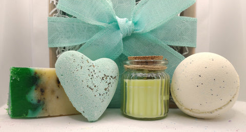 photo showing contents of gift set from left 1 handmade soap slice green and white with black flecks, 1 heart shaped bath fizzer light mint green with black flecks a light green candle in a glass jar with cork lid and twine and a yellow creamy coloured large bath bomb, shown in front of the hand tied gift box