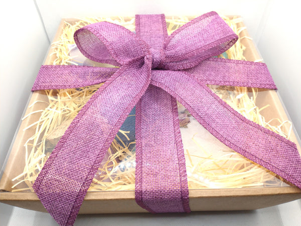 Photo shows a large kraft gift box with clear lid showing contents of gift set through a clear lid and a hand tied textured lavender ribbon tied off in a large bow