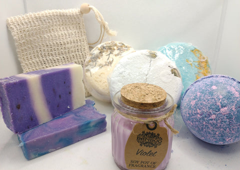 photo showing contents of the hamper 1 cream coloured jute soap soap bag with toggle, 1 lavender and white soap slice, 1 lavender and green soap slice, 3 large bath fizzers 1 white 1 cream and 1 blue all with floral patterns, a large violet and pink bath bomb and violet candle in a glass jar with cork lid and a kraft tag with writing Violet Soy Pot of Fragrance