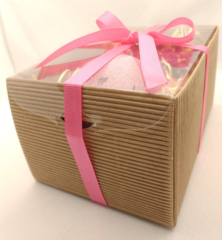 kraft brown corrugated gift box with pink handtied ribbon showing contents of pink bath bomb and pink handmade soap