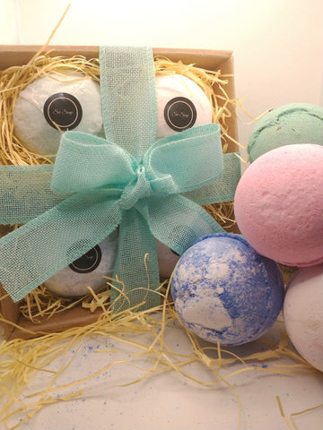 Bath Bomb Gift Set showing wrapped bath bombs on straw in a kraft gift box with hand tied ribbon and contents shown displayed in front