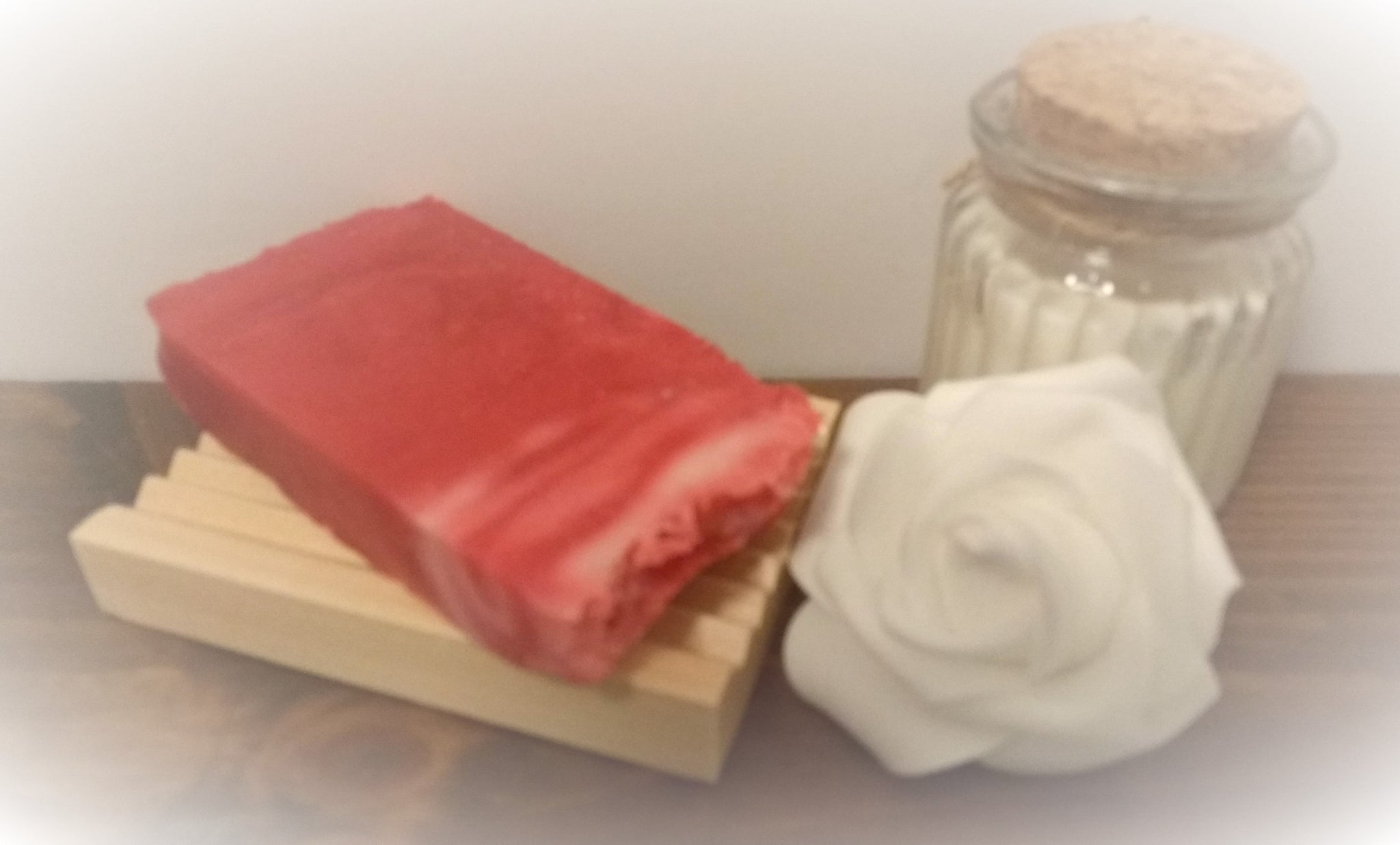 Pink Soap slice on soap dish displayed next to rose and candle