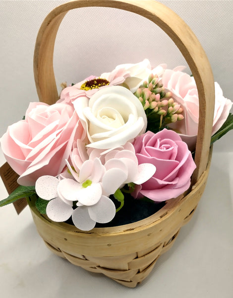 A wicker basket with handle containing beautiful soap flowers arranged in a bouquet style with green foliage flowers shown are a mix of pink and white roses and pink sunflowers