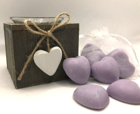 Cute purple heart shaped soy wax melts shown sat against a white clear organza bag containing purple heart shaped soy wax melts