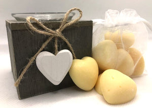 Cute yellow heart shaped soy wax melts shown sat against a white clear organza bag containing yellow heart shaped soy wax melts
