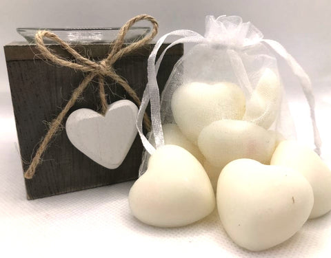 Cute white heart shaped soy wax melts shown sat against a white clear organza bag containing white heart shaped soy wax melts