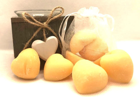 Cute orange heart shaped soy wax melts shown sat against a white clear organza bag containing orange heart shaped soy wax melts