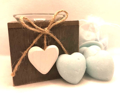 Cute blue heart shaped soy wax melts shown sat against a white clear organza bag containing blue heart shaped soy wax melts