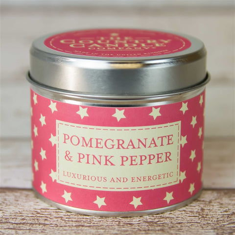silver round tin with pink and white stars band labelled Pomegranate & Pink Pepper with Pink sticker on lid with writing The Country Candle Candle Company