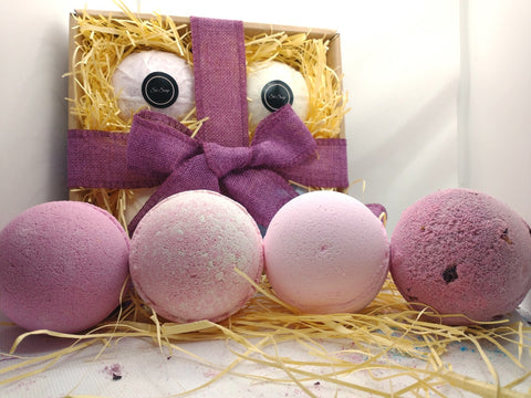 A beautifully handtied gift set containing wrapped bath bombs with the logo s6 soap presented in a brown gift box laid on a bed of straw with a purple hand tied ribbon.  In front of the gift box are 4 pink bath bombs