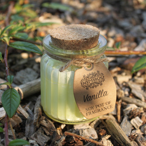 Candle in a glass jar with cork lid on bark chippings
