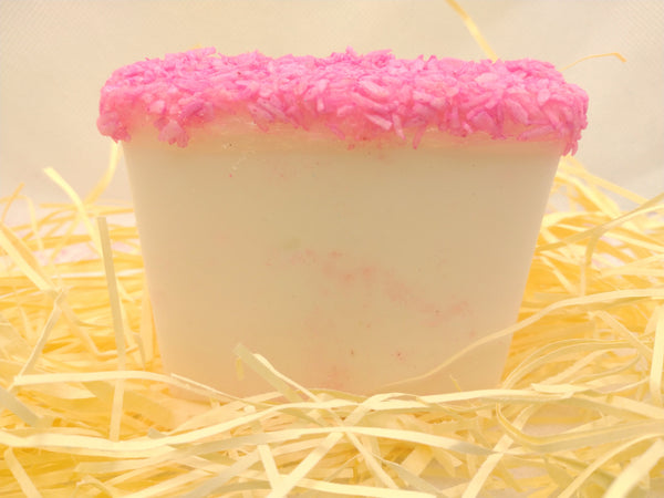 natural soap slice white in colour topped wih pink coconut displayed on a bed of straw