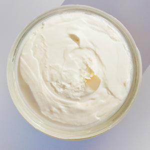 a close up shot of the off white body butter displaying it has a ultra smooth consistency