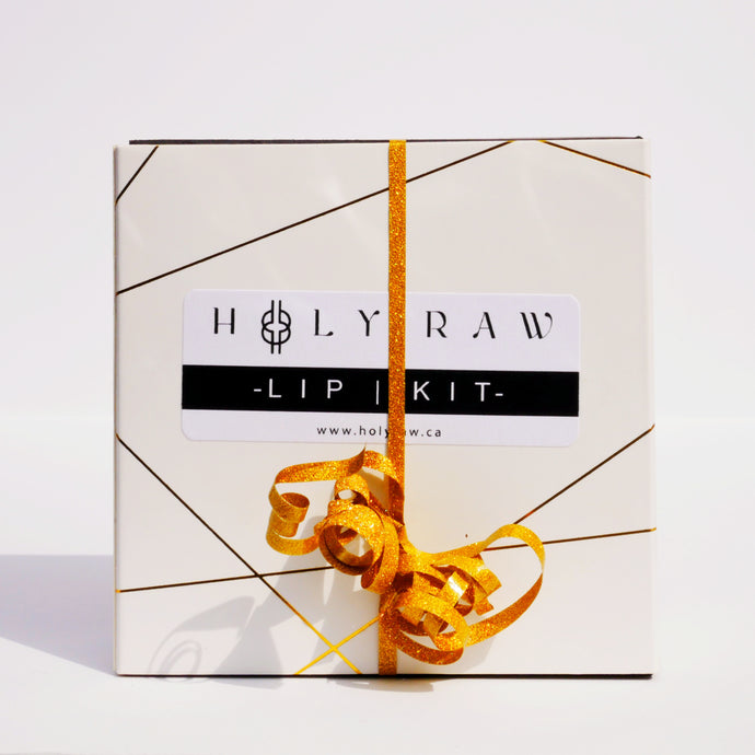 The Holy Raw lip kit off white box with a gold ribbon and abstract metallic gold lines across the box