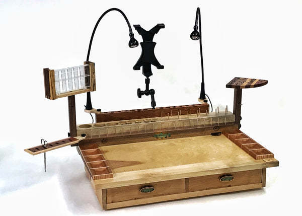 The two drawer Rainbow fly tying bench with a trash drop hole in the right rear corner. The dubbing dispenser swivel is an accessory that can be added to the bench on the opposite end of the tool swivel plate.  These can be mounted on either side of the bench using two thumb screws. The photo also shows the other accessories that can be added to the bench.