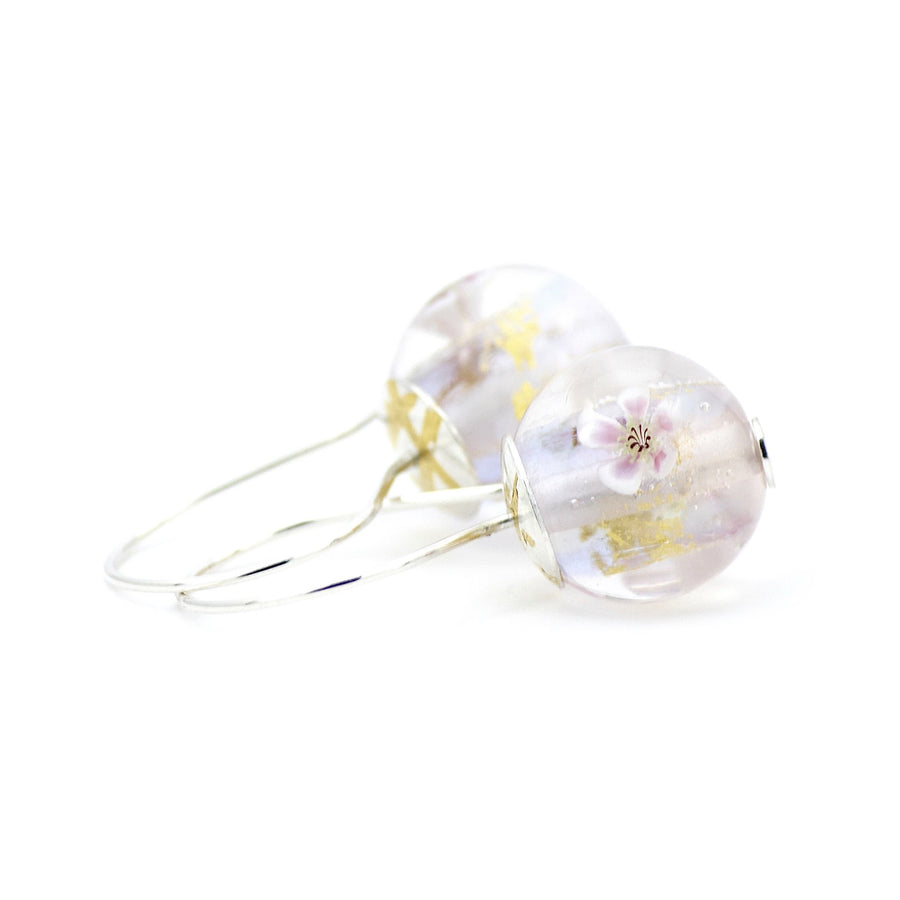 Pale lilac, pink and opal flameworked glass earrings featuring fragments of 24K gold leaf and tiny white apple blossoms. These lightweight earrings are finished with sterling silver ear wires and sterling silver bead caps with 23.5K gold foil Keum Boo accents.