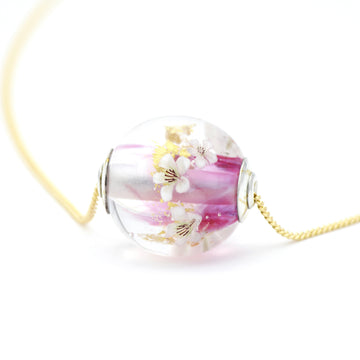 "Pink, opal and clear flameworked glass pendant featuring tiny glass apple blossoms (floral murrine) and fragments of 24K gold leaf.  This pendant is finished with sterling silver caps embellished with 23.5K gold foil accents and hangs on an 18"" long 14/20 gold fill chain."