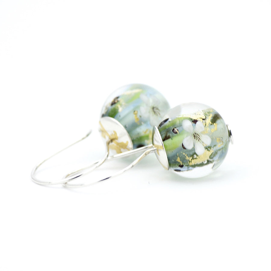 Green and opal flameworked glass earrings featuring fragments of 24K gold leaf and tiny white apple blossoms. These lightweight earrings are finished with sterling silver ear wires and sterling silver bead caps with 23.5K gold foil Keum Boo accents.