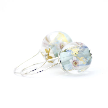 Blue, pale aquamarine blue and opal flameworked glass earrings featuring fragments of 24K gold leaf and tiny white apple blossoms. These lightweight earrings are finished with sterling silver ear wires and sterling silver bead caps with 23.5K gold foil Keum Boo accents.