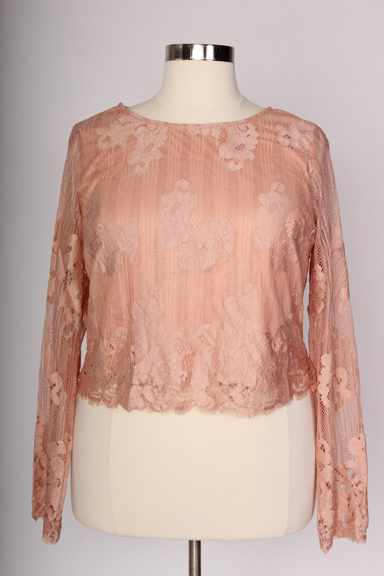 The perfect addition to its matching lace skirt and just as easily paired with a tutu for some more festive vibes, this lace top is as versatile as they come. The blush color is perfect in every season and the details of the lace along with the long sleeves ooze class. Dress it up, or play it more demur, whatever you decide, we know you'll look absolutely wonderful. Fit note: the sleeve is not fitted and has room if you're looking for wide sleeves. SHELF: 90% Polyester, 10% Nylon LINING: 100% Polyester Hand wash cold Hang dry Imported Front length Back length Arm hole Size:12/14 20