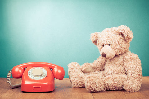 Teddy Bear next to Red telephone depicting Contact Us