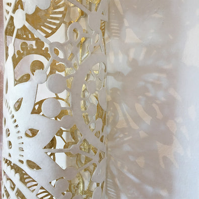 A close up showing the detailed design on this white and gold textile sculpture by Jennifa Chowdhury, created to portray peace, purity and godliness.