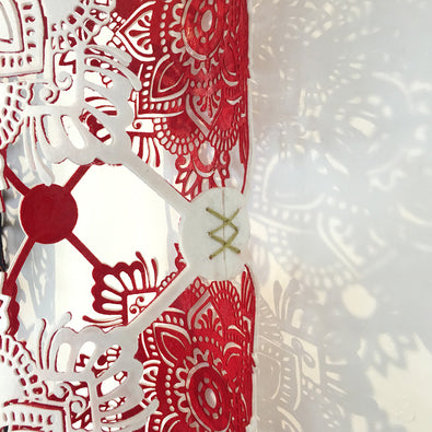 A close up showing the detailed design on this red and white textile sculpture by Jennifa Chowdhury, inspired by 'Laal Paar' sarees.