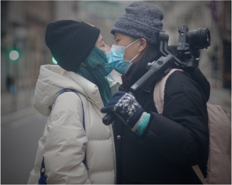 Two queer Chinese people kissing in the street. Both wearing puffy coats and beanie hats, while wearing blue surgical face masks. One is carrying a camera.