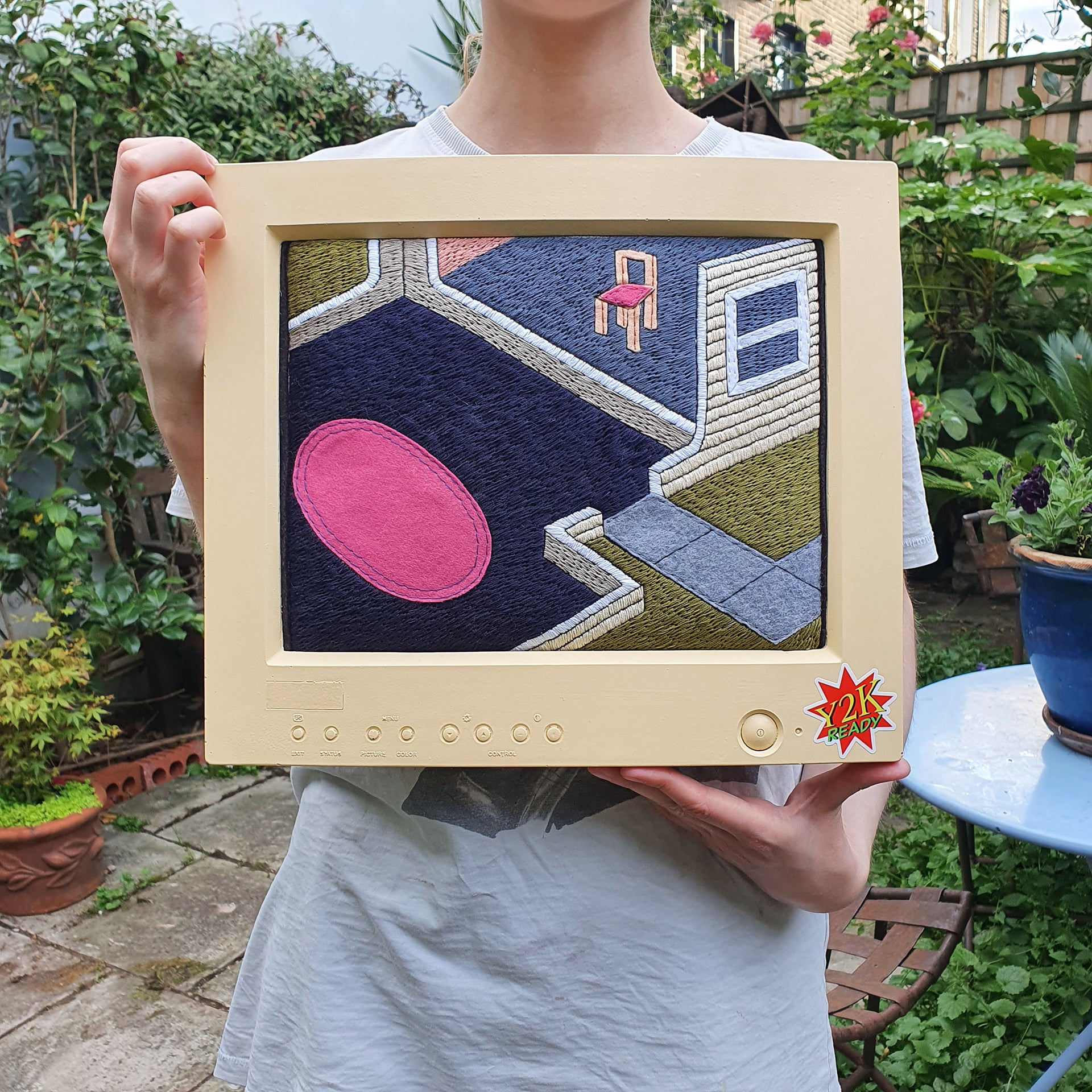 The artist holding the 'AFK Series 2: Living Room' artwork, while stood in her garden.