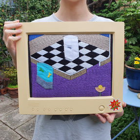 The artist holding the 'AFK Series 2: Kitchen' artwork, while stood in her garden.