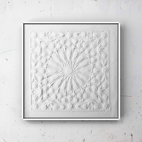 White laser cut textile artwork in a white square frame on a white, scratched background. The artwork has layers of white felt to form an Islamic, symmetrical pattern.
