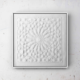 Framed artwork of intricate white Laser Cut Textile pieces layered to create a geometric design inspired by traditional Islamic Art.