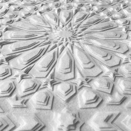A closer look at the detail in this layered, white, laser cut textile design by Jennifa Chowdhury for Shiver Art Gallery, shown from an angle.