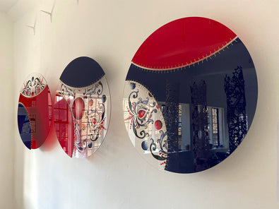 3 circular textile artworks by Jennifa Chowdhury made of acrylic and gold thread, each split into 3 sections of red, navy and transparent patterned section.