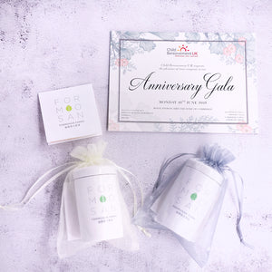 overhead shot of two white tea caddies wrapped in see through lace with certificate placed above them
