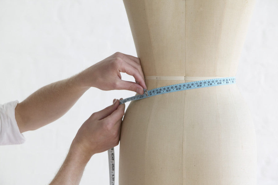 A person measuring a mannequin