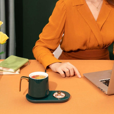 a girl using a laptop while coffee being heated in the mug warmer