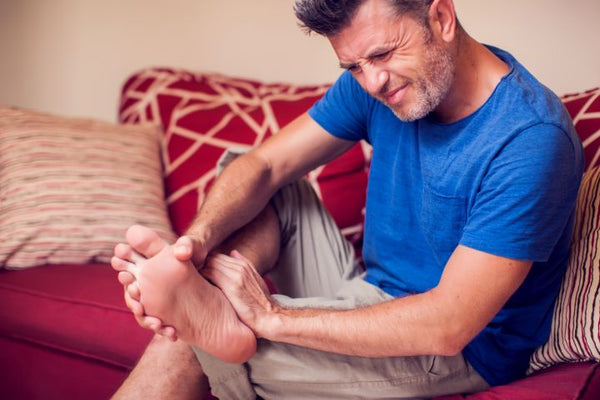 Man experiencing a painful foot cramp