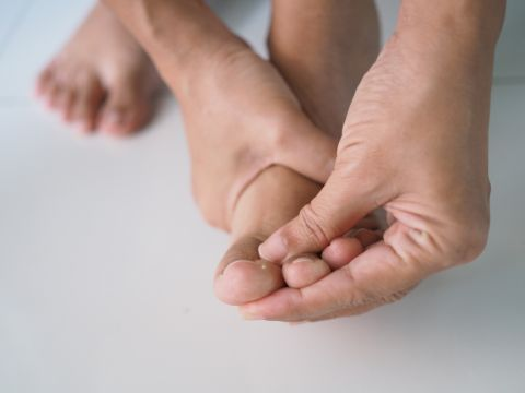 A person rubbing their foot to ease the chronic foot pain caused by diabetic neuropathy