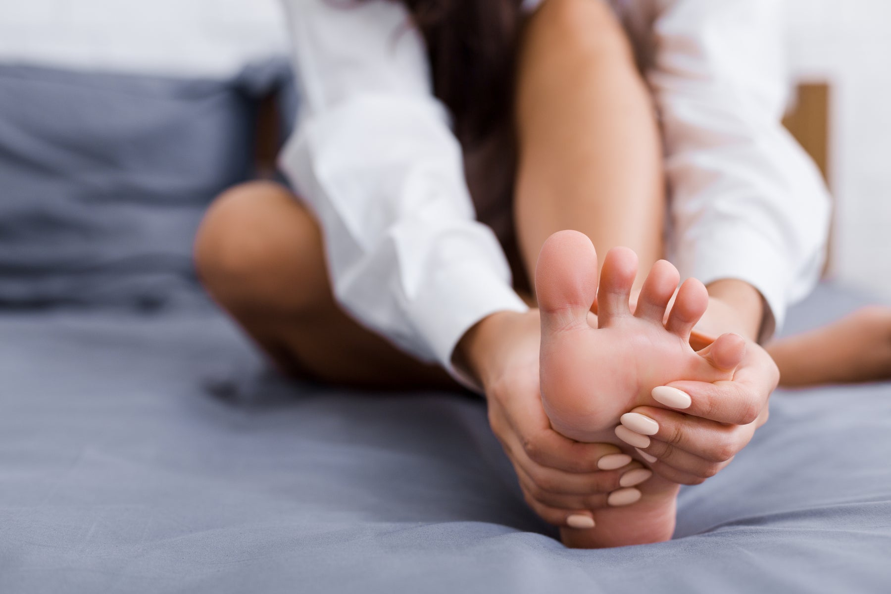 Woman giving herself a foot massage in bed.